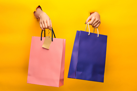 Female hand holding bright shopping bags Stock Photo