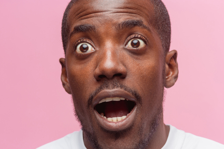 The portrait of handsome young surprised black african man Фото со стока