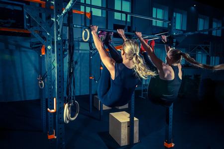 コンセプト: パワー、強さ、健康的なライフスタイル、スポーツ。クロスフィットジムで強力な魅力ある筋肉の女性