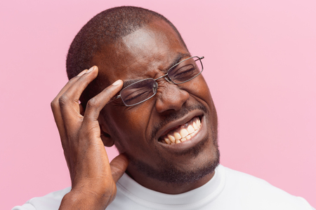 Black man holding his head in pain and depression