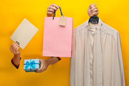 Female hand holding bright shopping bag and gifts Stock Photo