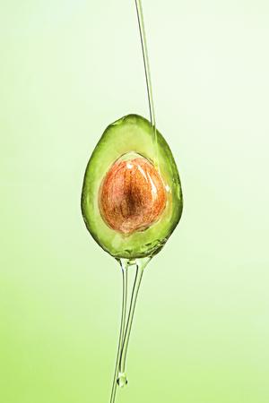 Avocat frais et huile sur fond vert