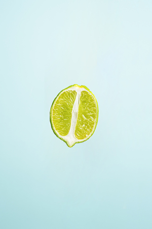 slice of lime isolated on blue background
