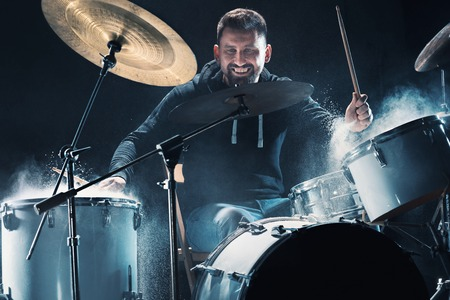 Drummer die op trommels vóór rockconcert repeteert. Mensenopnamemuziek op drumstel in studio
