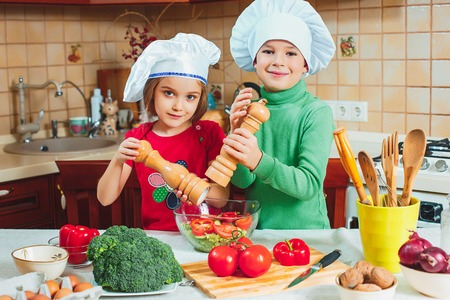 happy family funny kids are preparing the a fresh vegetable salad in the kitchen