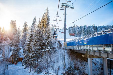 雪に覆われた斜面や森林、ブコヴェリ、ウクライナの丘の美しい背景を持つスキーに乗ってスキー場のリフトのスキーヤー 写真素材