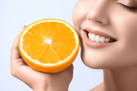 Beautiful womans face with juicy orange Zdjęcie Seryjne - 90140792
