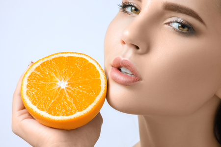 Beautiful womans face with juicy orange