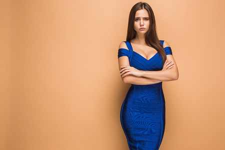Beautiful young brunette woman posing in a blue dress. Studio Stock Photo - 90339383