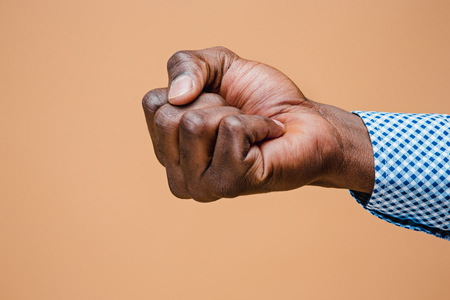 Male black fist isolated on brown background. African american clenched hand, gesturing up