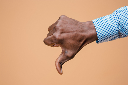 Thumb down hand sign on brown, seal of disapproval Standard-Bild