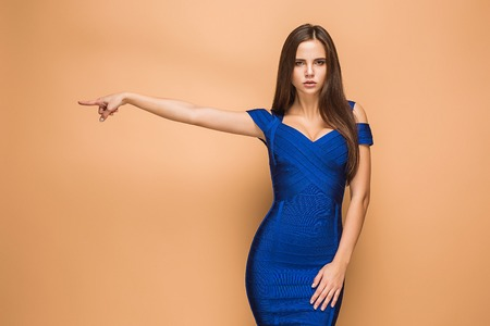 Beautiful young brunette woman posing in a blue dress. Studio Stock Photo
