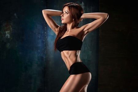 Muscular young woman athlete on black Stockfoto