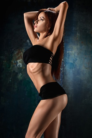 Muscular young woman athlete on black Stock Photo