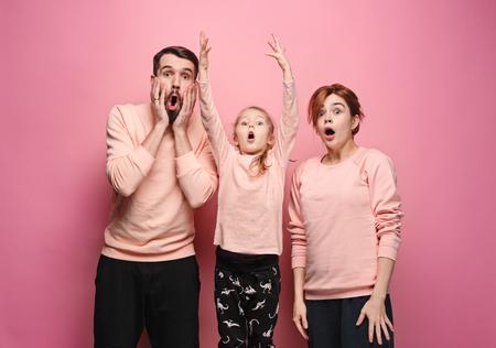 surpris jeune famille regardant la caméra sur rose