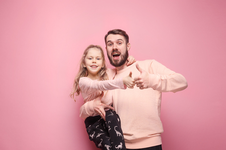 Young father with his baby daughter with thumb up