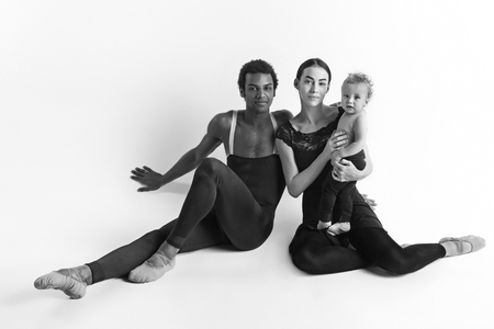 A happy family of ballet dancers on white studio background