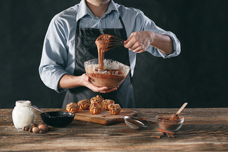 Decorating delicious homemade eclairs with chocolate and peanuts Stock Photo