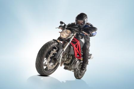 Biker in black jacket and helmet sitting on his sportive bike on blue background