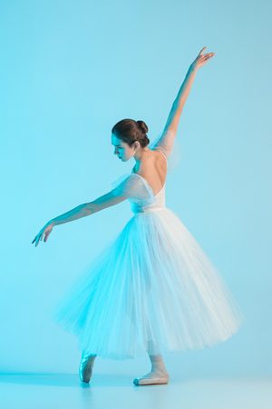 Young and incredibly beautiful ballerina is dancing in a blue studio Stock Photo