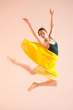 若くて信じられないほど美しいバレリーナはスタジオで踊っています
