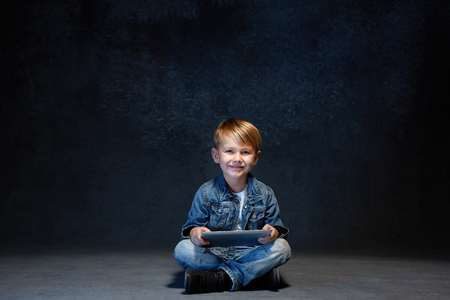Little boy sitting with tablet in studio