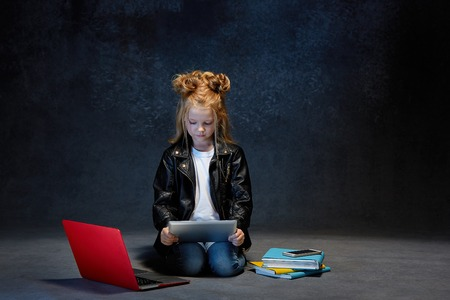 Little girl sitting with gadgets Imagens