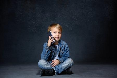 Little boy sitting with smartphone in studio
