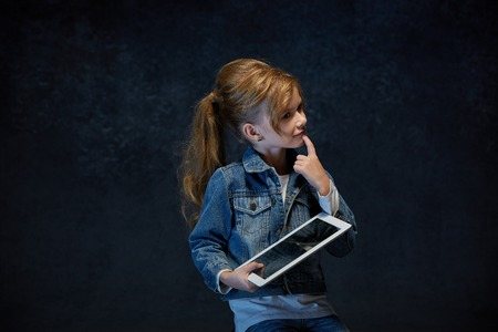 Little girl sitting with tablet