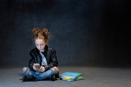 Little girl sitting with smartphone in studio