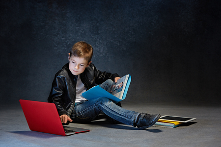 Little boy sitting with gadgets