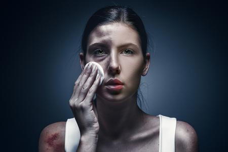 상처 입은 피부와 검은 눈을 가진 우는 여성의 초상화를 닫습니다.