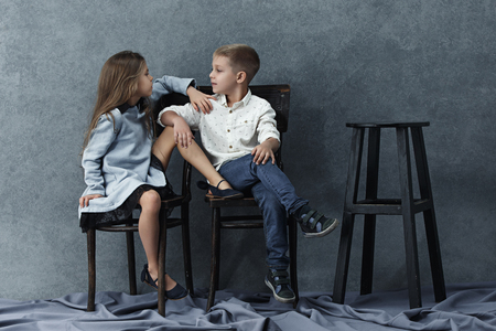 A portrait of little girl and a boy on the gray background