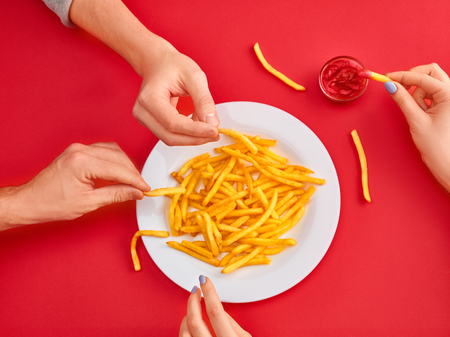 Young woman eating french fries potato with ketchup in a restaurant 版權商用圖片
