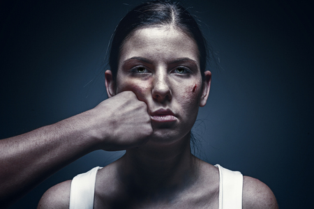 Male fist against kidnapped young woman in the background Stock Photo