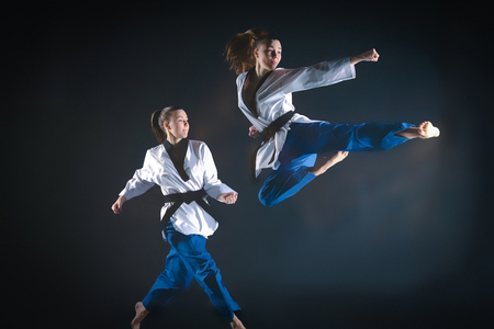 The karate girl in white kimono and black belt training karate over gray background. Stroboscope shooting technique Stock Photo