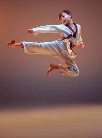 Young boy training karate on blue background Stock fotó