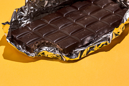 Bitten Chocolate bar in foil isolated on yellow background. Фото со стока - 92241113