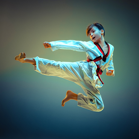 Młody chłopak trenuje karate na niebieskim tle Zdjęcie Seryjne