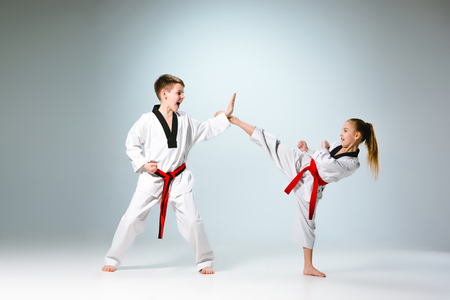 The studio shot of group of kids training karate martial arts Фото со стока
