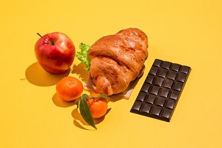 黄色の背景にリンゴ、チョコレート、クロワッサン
