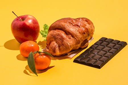 The apple, chocolate and croissants on yellow background 写真素材