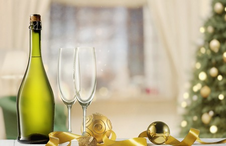 Glasses with champagne and bottle over sparkling holiday background Stock Photo