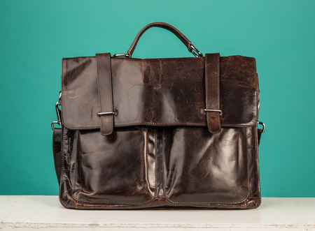 A vintage leather briefcase on a blue background