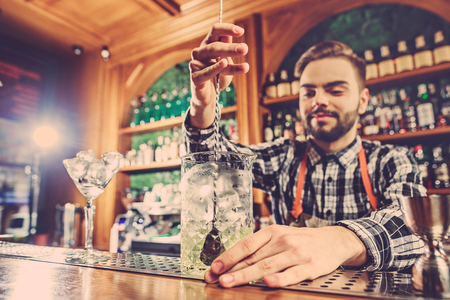 Barman making an alcoholic cocktail at the bar counter on the bar background