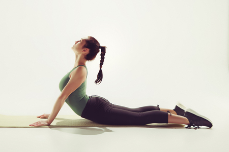Beautiful slim brunette doing some stretching exercises in a gym