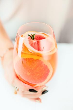 De roze exotische cocktails en fruit en vrouwelijke hand