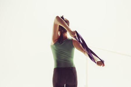 The brunette athletic woman exercising with rubber tape 写真素材