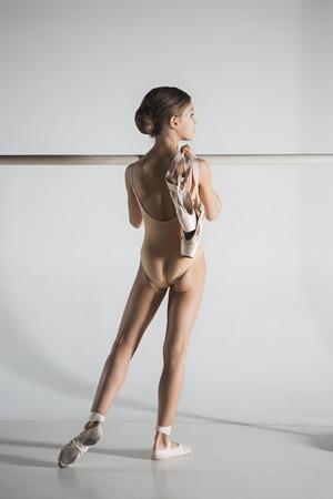 Das Mädchen trainiert in der Nähe der Ballettstange. Standard-Bild - 93387711