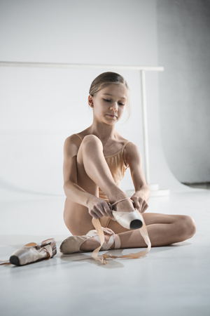 Beautiful little ballerina in blue dress for dancing puting on foot pointe shoes Zdjęcie Seryjne
